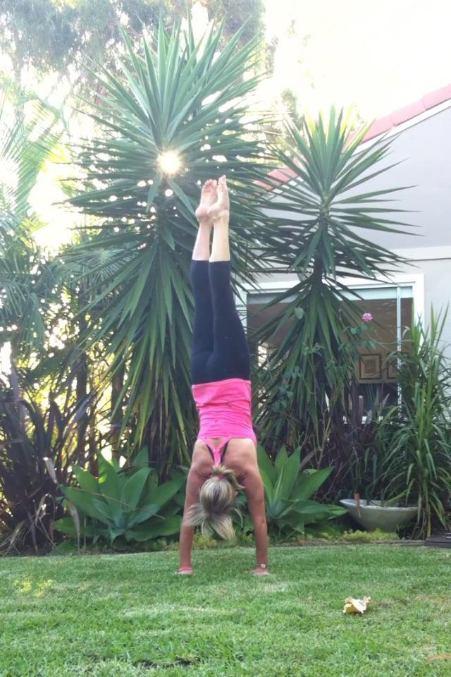 Martine Ford of Spirit Yoga practicing a handstand in the garden