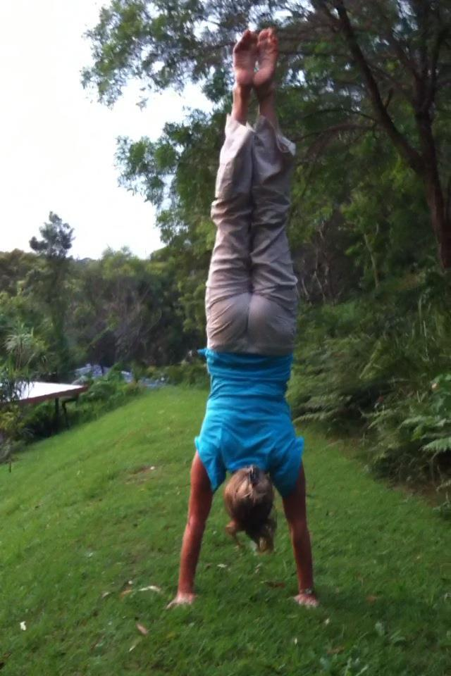 Martine Ford of Spirit Yoga practicing a handstand on a hill
