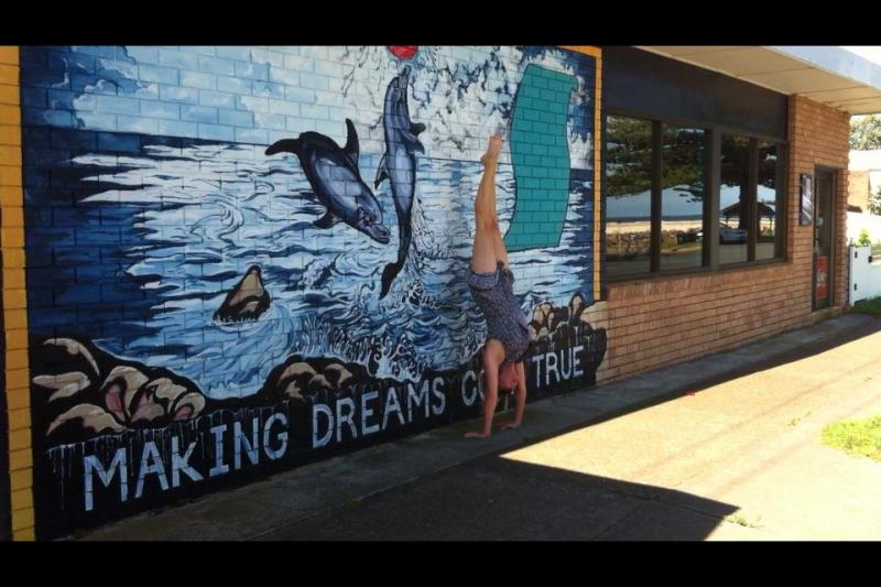 Martine Ford of Spirit Yoga practicing a handstand next to a mural