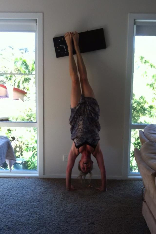 Martine Ford of Spirit Yoga practicing a handstand & knocking over a clock