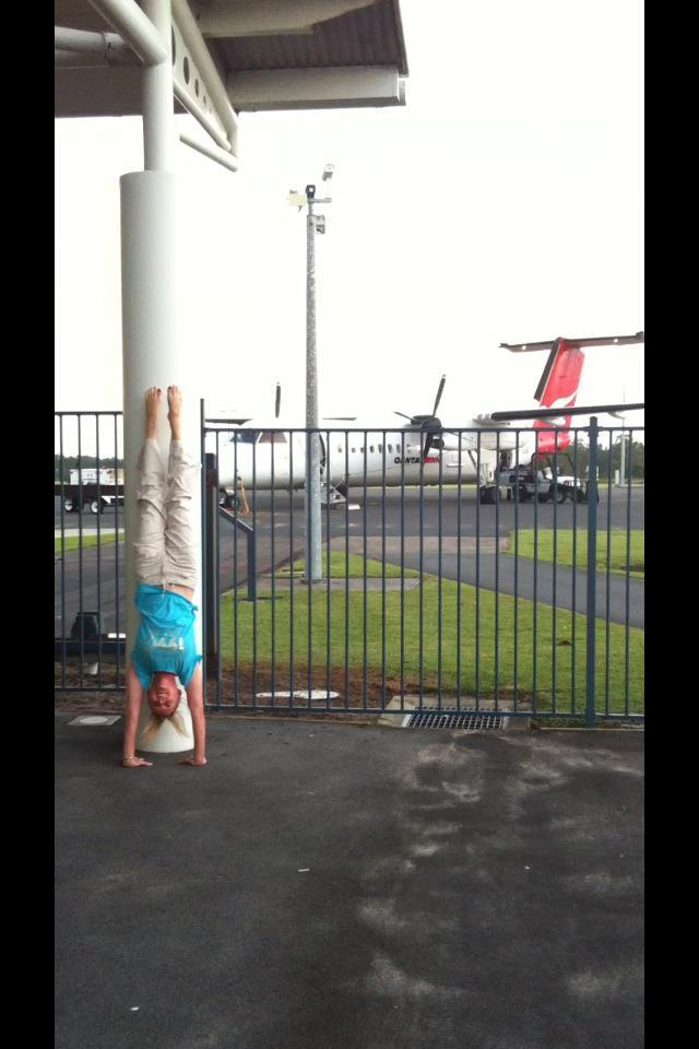 Martine Ford of Spirit Yoga practicing a handstand at the airport