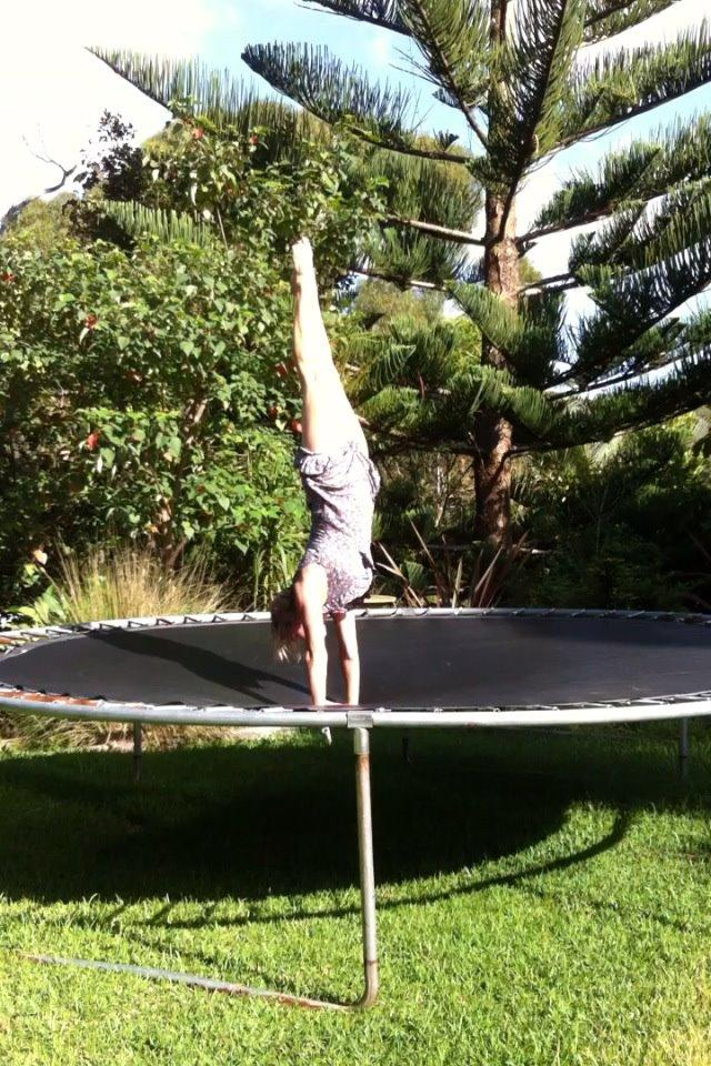 Martine Ford of Spirit Yoga practicing a handstand on a trampoline