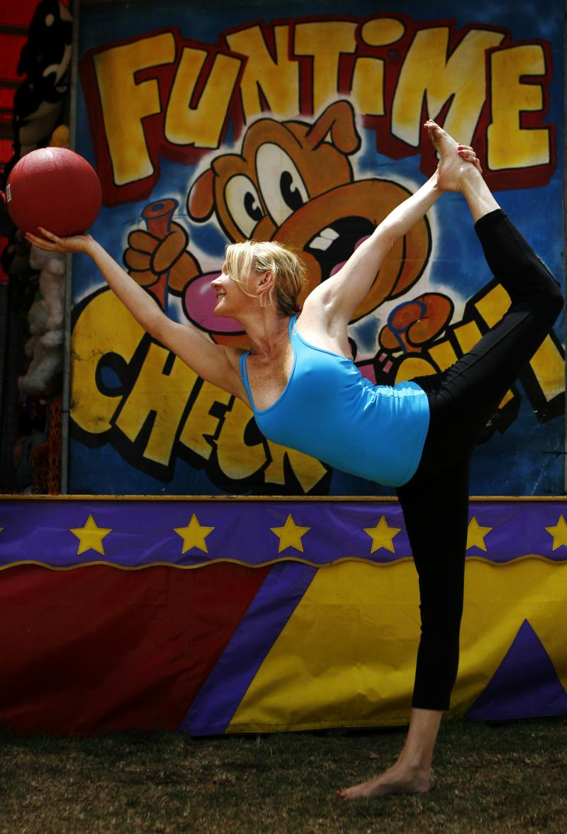 Martine Ford of Spirit Yoga in Dancers Pose holding a basket ball at the Circus.
