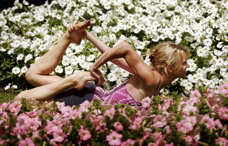 Martine Ford of Spirit Yoga in Gherandasana Pose amongst flowers
