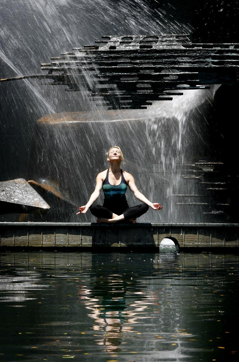 Martine Ford of Spirit Yoga meditating in front of water fall feature.