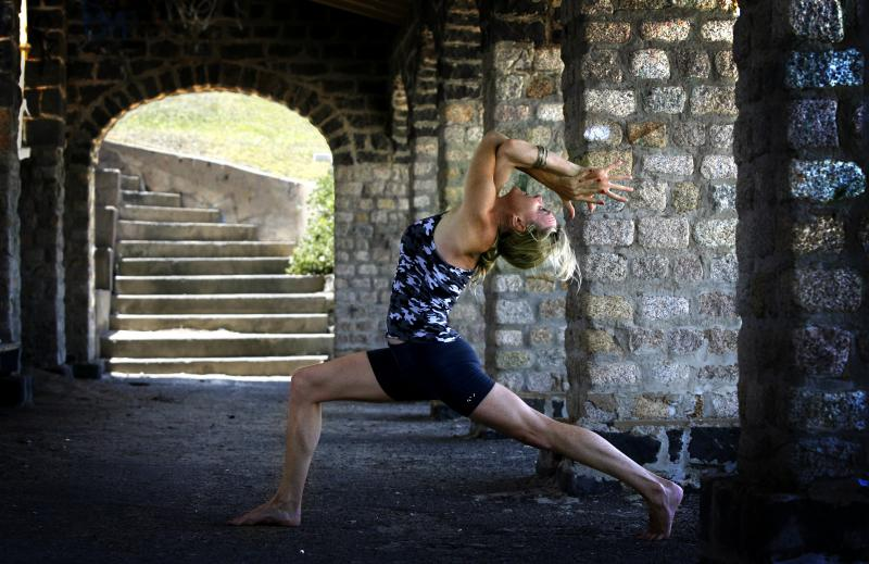 Martine Ford of Spirit Yoga in Eagle Lunge Backbend near arch staircase.