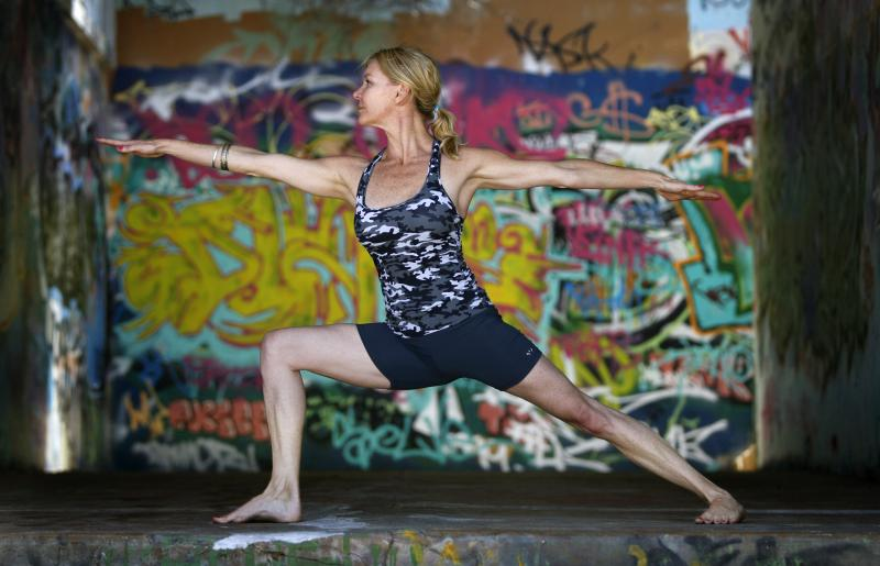 Martine Ford of Spirit Yoga in Warrier 2 Pose in front of colourful grafitti.