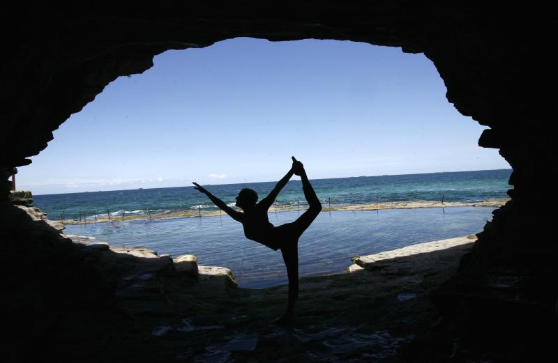 Martine Ford of Spirit Yoga in Dancers Pose in a cave near the ocean.