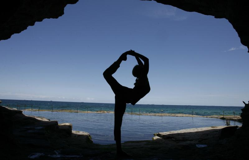 Martine Ford of Spirit Yoga in Full Dancers Pose in a cave near the ocean.