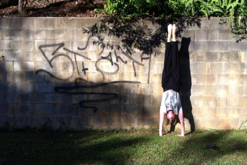 Martine Ford of Spirit Yoga practicing a handstand next to graffiti