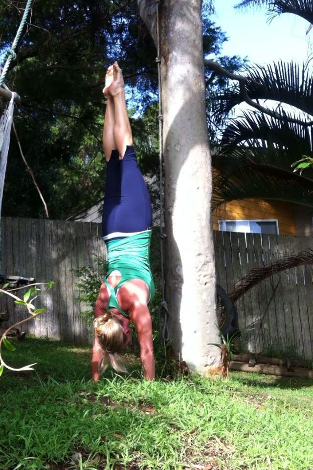 Martine Ford of Spirit Yoga practicing a handstand next to a tree