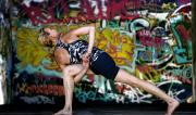 Martine Ford of Spirit Yoga in Bound Revolved Crescent Lunge amongst graffiti.