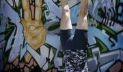 Martine Ford of Spirit Yoga in Tripod Headstand next to a peace mural