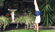 Martine Ford of Spirit Yoga practicing a handstand next to another birdbath