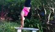 Martine Ford of Spirit Yoga practicing a handstand on a bench seat